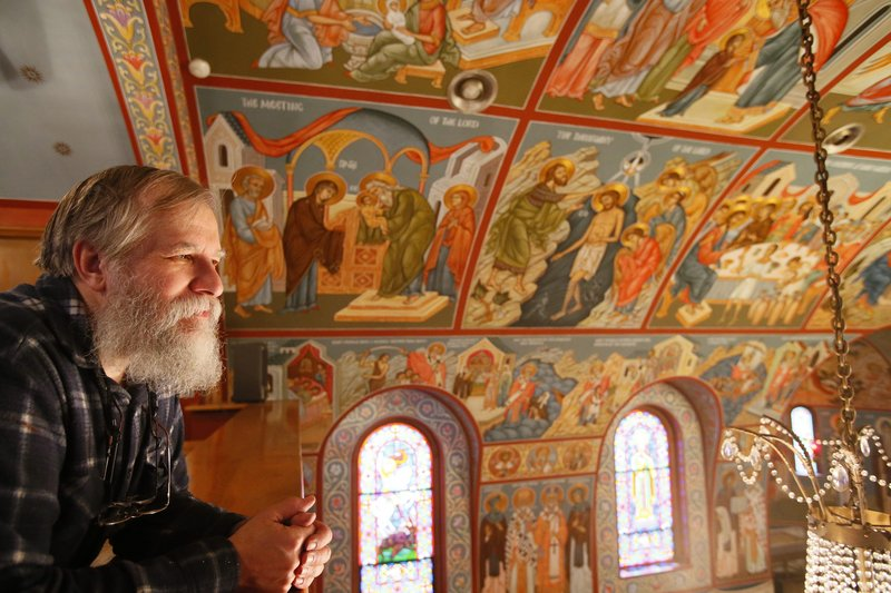 The Rev. Theodore Jurewicz looks over the icons he painted over the last six years.