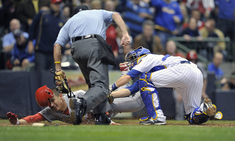 Allen Craig of the St. Louis Cardinals is closely watched by umpire Dale Scott as he's tagged out by Milwaukee's Jonathan Lucroy during a 6-1 win by the Cardinals at Milwaukee on Friday.