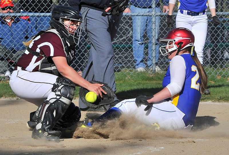 Elizabeth Walker of Falmouth slides in to score as Greely catcher Audrey Mann tries to control the ball. Walker's triple in the sixth inning was the game-winner.