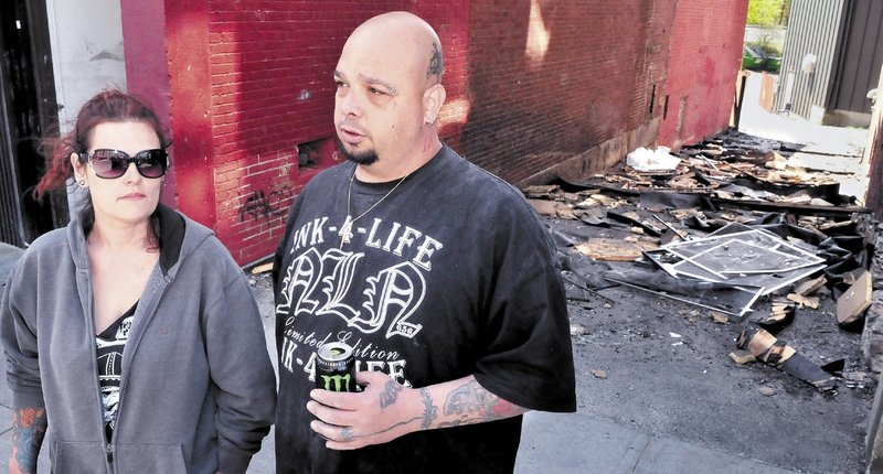 Mona and Bill Juliano, owners of INK-4-LIFE tattoo parlor, speak outside an alley Monday that was littered with debris from the fire that destroyed their business . They are relocating across Main Street.