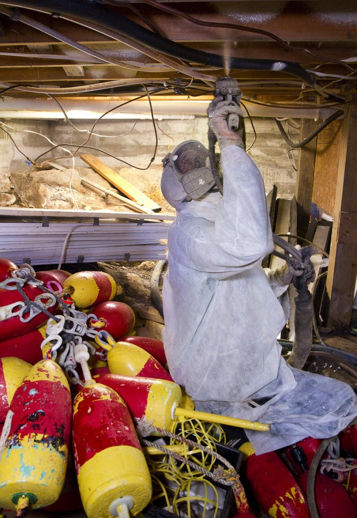 Brandon Currie of C & C Spray Foam of Clinton applies spray insulation to seal leaks beneath a Monhegan Island home.