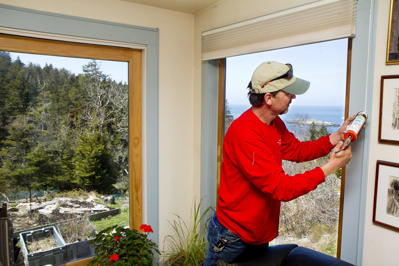 Scott Braley caulks a window frame to make a Monhegan Island home more energy efficient.
