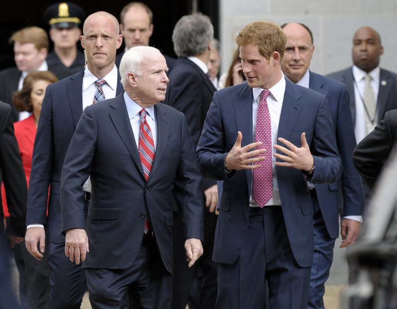 Prince Harry talks with Sen. John McCain, R-Ariz., as they leave the Russell Senate Office Building.