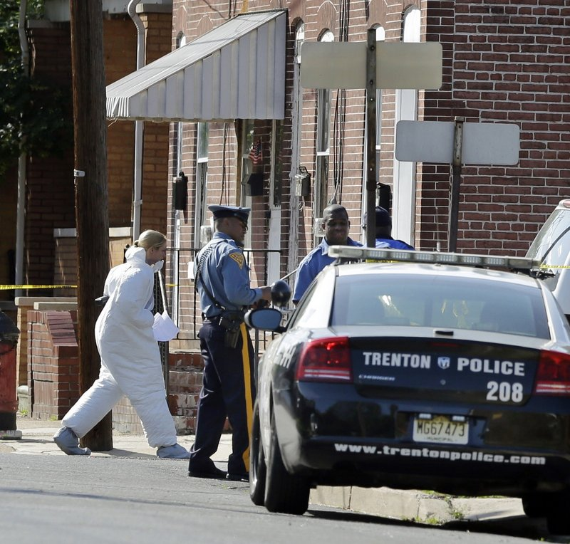 An investigator in protective clothing walks near the scene in Trenton, N.J., where a registered sex offender who held his girlfriend's three children hostage was shot to death Sunday. Police rescued the children and recovered the bodies of their mother and a sibling.