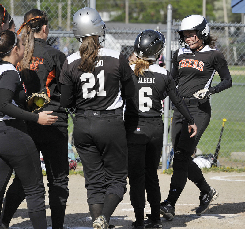 Katelyn Lebreaux, right, of Biddeford is greeted by teammates after hitting a two-run home run in the second inning of the Tigers' 7-1 win over Westbrook on May 13.