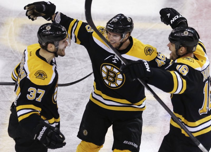 Boston center Patrice Bergeron, left, is congratulated by David Krejci, center, and Nathan Horton after his last-minute goal set up overtime Monday vs. Toronto.