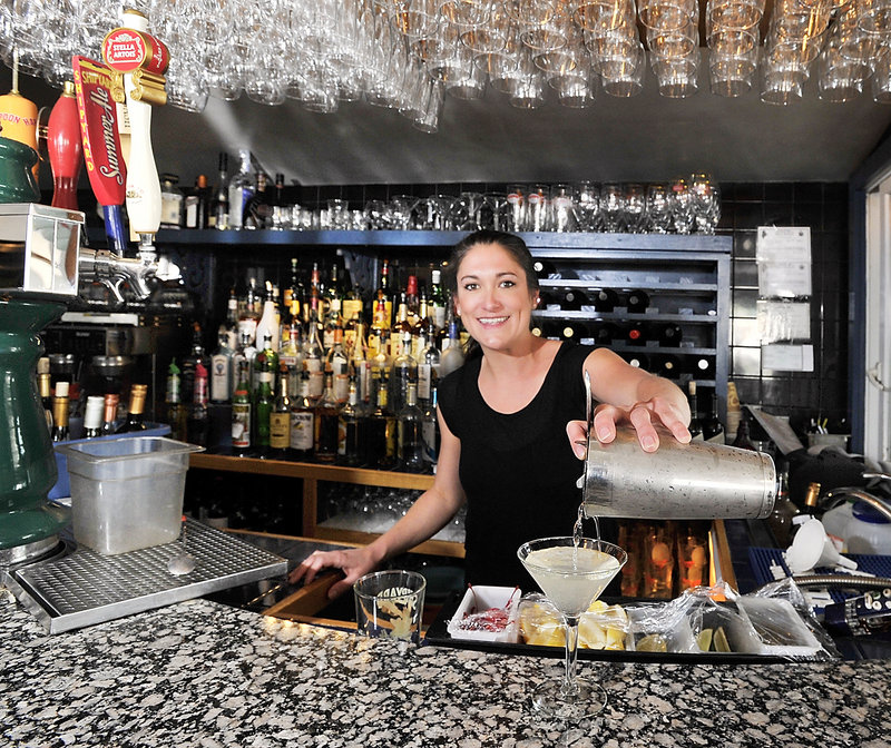 Kelsey Sirois, a waitress and bartender at Joe's Boathouse on the waterfront in South Portland, makes a Dirty Martini. The restaurant's bar is small, but in summer, an outdoor deck provides a scenic spot for sipping.