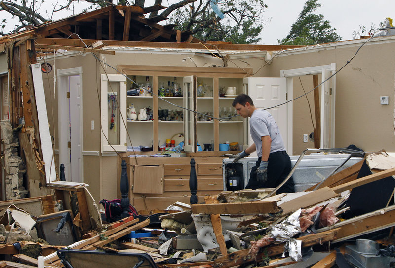 A rescue worker searches through debris Thursday after a tornado swept through the town of Granbury, Texas, late Wednesday. At least six people were killed and dozens injured as tornadoes ripped through a stretch of Texas near the Dallas-Fort Worth area.