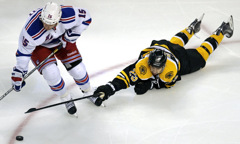 It's a stretch for Bruins center Chris Kelly, who tries to knock the puck away from Rangers right wing Derek Dorsett during first-period action in Boston.