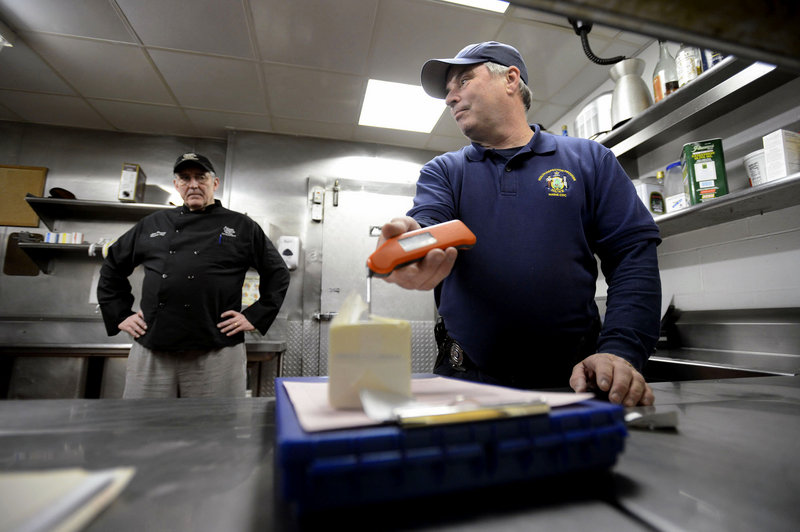"Scott Davis, a state health inspector, checks the temperature of food stored in a walk-in cooler in the kitchen at the Stage Neck Inn in York Harbor as executive chef Lynn Pressey looks on. ""He knows we're trying to do the right thing."" Pressey said."