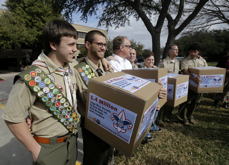 James Oliver, left, hugs his brother and fellow Eagle Scout Will Oliver, who is gay, as Will and other supporters carry four boxes filled with a petition to end the ban on gay scouts in February in Dallas.