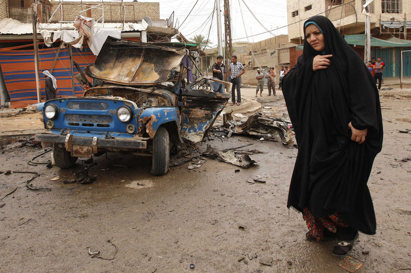 An Iraqi woman passes by the scene of a car bomb attack in a predominantly Shiite area of eastern Baghdad on Monday. A wave of car bombings across Baghdad's Shiite neighborhoods and in the southern city of Basra killed dozens of people, police said.