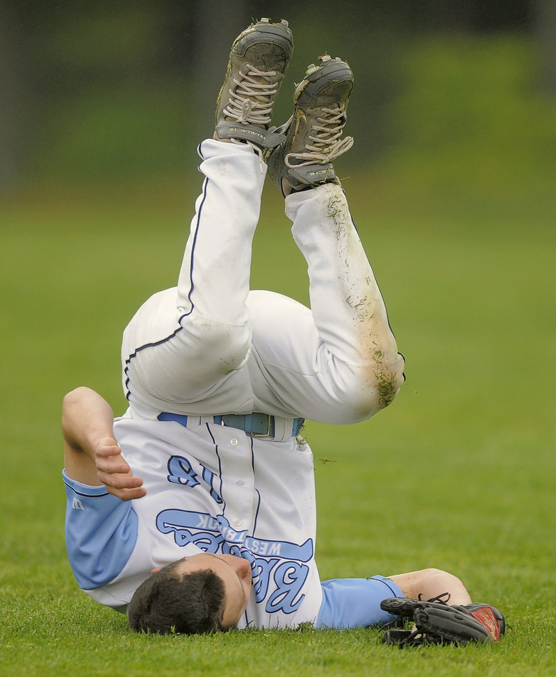 Ryan Gilligan of Westbrook ends up on his head Tuesday after making an acrobatic catch in left field during the SMAA game against Windham, which pulled away to a 7-2 victory.