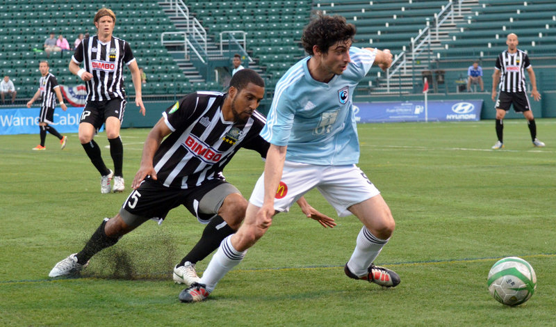 Clement Bompart of the Portland Phoenix, right, looks to make a play Tuesday night after slipping past Ross LeBauex of the Rochester Rhinos during their second-round game in the U.S. Open Cup. Rochester won, 1-0.