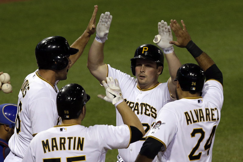 Pittsburgh's Travis Snider is greeted at the plate by the three runners he delivered with a grand slam in the sixth inning of Pittsburgh's 5-4 win over the visiting Cubs on Tuesday.