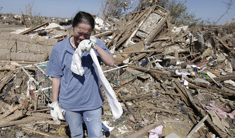 Kriket Krekemeyer weeps while digging through the remains of her tornado-ravaged home in Moore, Okla., Wednesday. The tornado may have created $2 billion or more in damage as it tore through as many as 13,000 homes, multiple schools and a hospital.