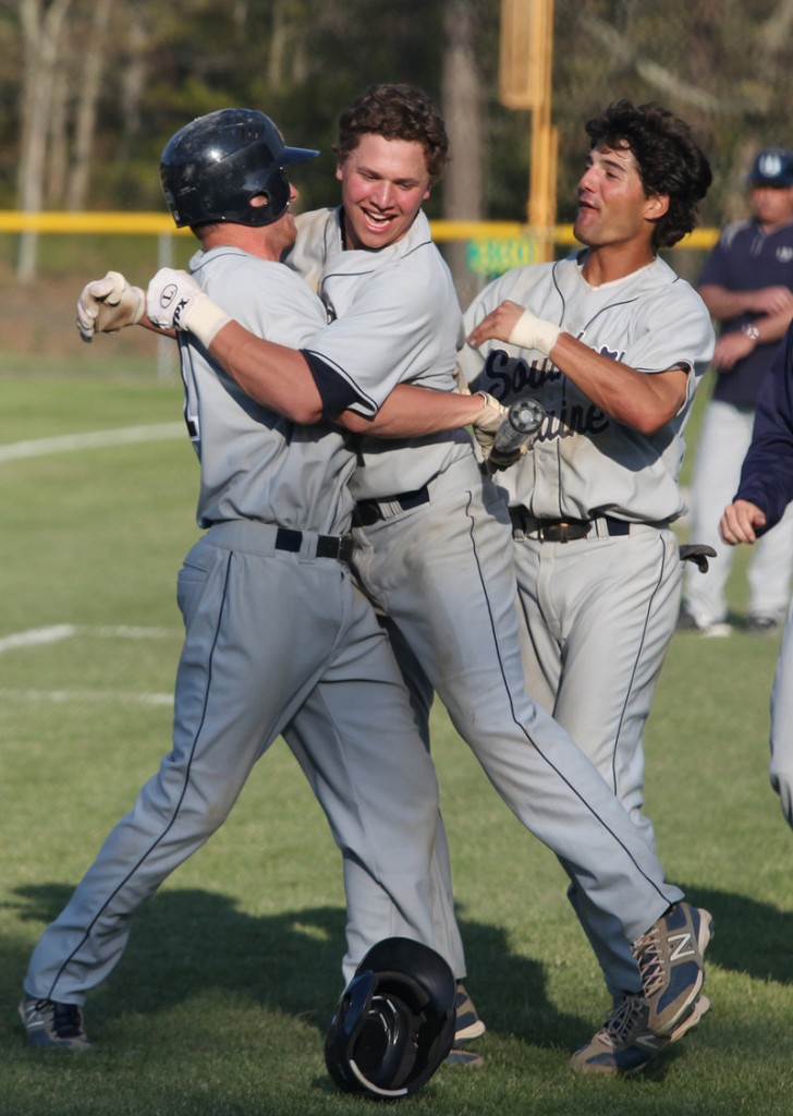 USM's Sam Dexter, center, celebrates a tie-breaking home run Saturday against Endicott College that helped the Huskies win the NCAA Division III regional title.
