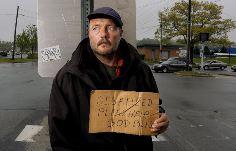 Don Dietz, 48, panhandles for change in the median at the corner of Franklin Street and Marginal Way on Friday, May 24, 2013.