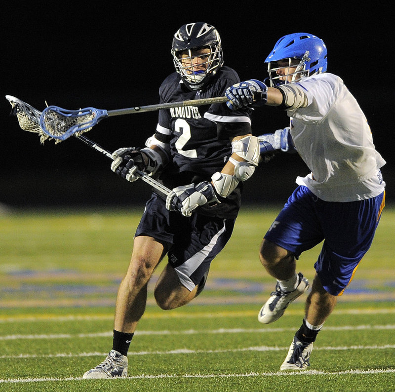 Quinn Hathcock of Yarmouth looks to work his way toward the goal Friday night while being defended by Brad Gilbert of Falmouth during their schoolboy lacrosse game. Yarmouth rallied late in regulation, then scored in overtime for a 15-14 victory.