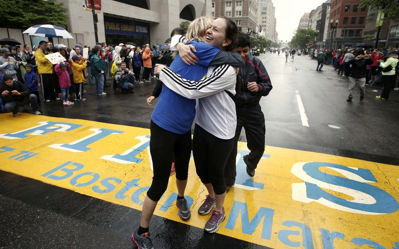 Rachel, left, and Pam Vingsness of Newton, Mass., embrace after crossing the finish line of the Boston Marathon. The two runners were unable to finish the marathon April 15 because of the bombings and were allowed to finish the last mile of the race with thousands of others in Boston on Saturday.