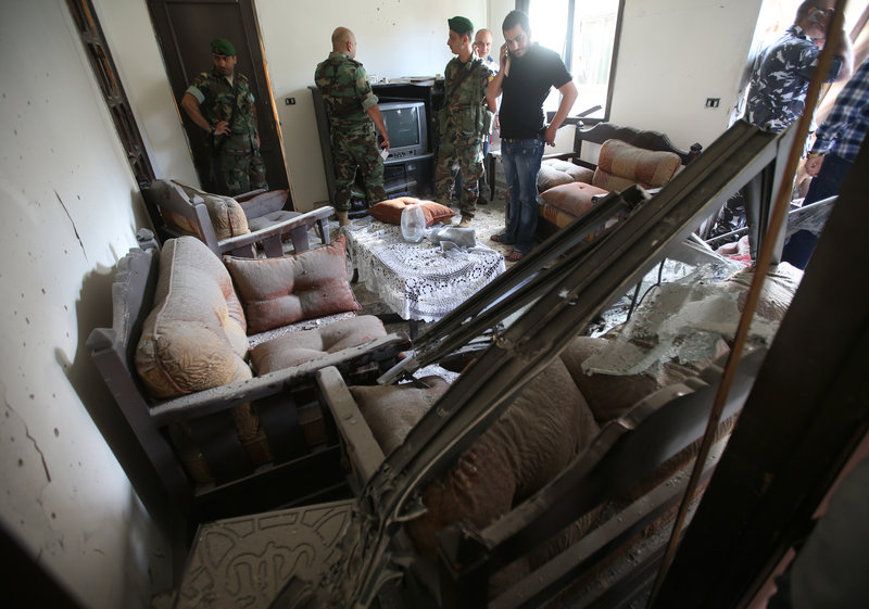 Lebanese army soldiers investigate after a rocket struck an apartment in Chiyah district, south of Beirut, Lebanon, on Sunday.