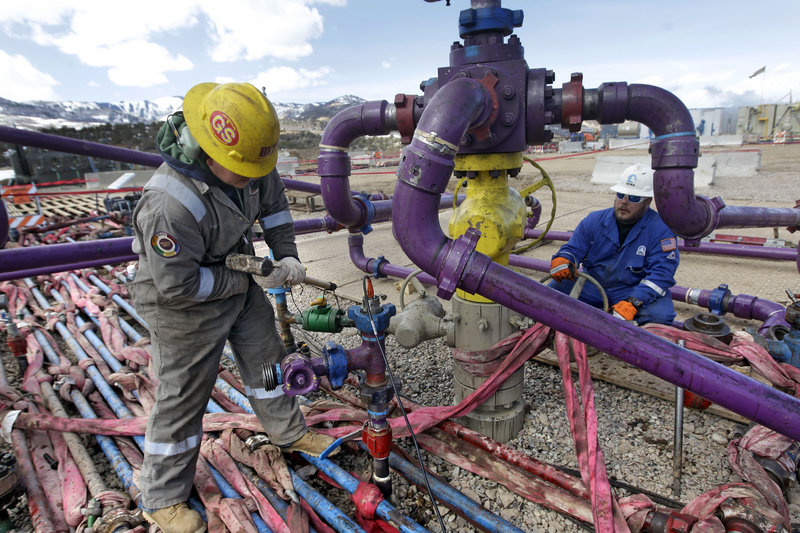 Workers tend to a well head at a hydraulic fracturing, or fracking, operation in Colorado. General Electric hopes its research can help reduce environmental impacts of the drilling.