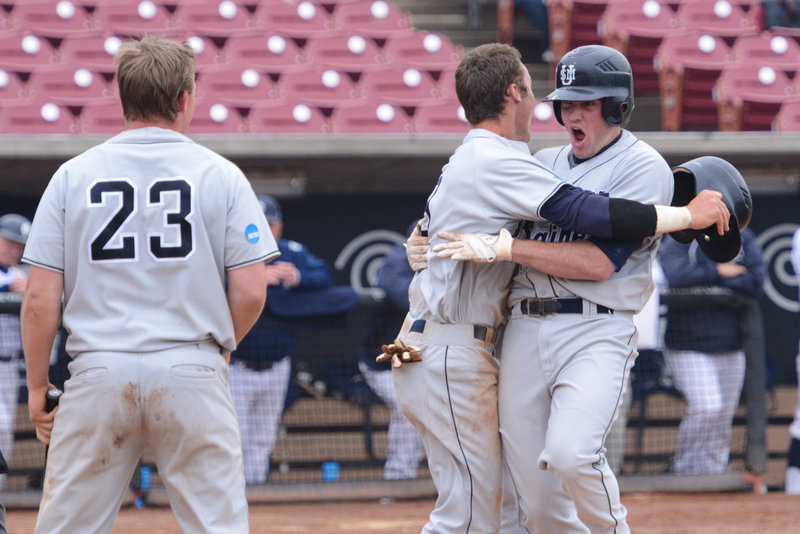 Chris Bernard is greeted after hitting what appeared to be a home run for USM in the 13th inning. One problem: Bernard never touched the plate and was ruled out. In the end, it didn't matter.
