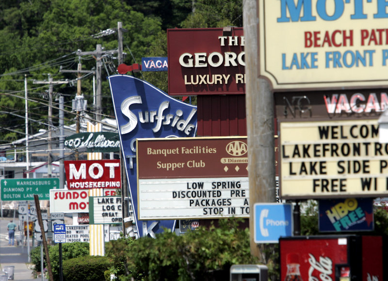 Motel signs line a road in Lake George, N.Y., a popular vacation destination. Airlines, hotels and campgrounds are likely to see slightly more customers in 2013 than in the previous few summers, according to travel industry forecasters.