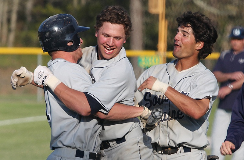 Sam Dexter, center, celebrates with teammates, including Anthony Pisani, right, after hitting a tiebreaking two-run homer in the ninth inning Saturday to propel Southern Maine to a 5-2 win over Endicott in the championship round of the NCAA Division III baseball regionals at Harwich, Mass.
