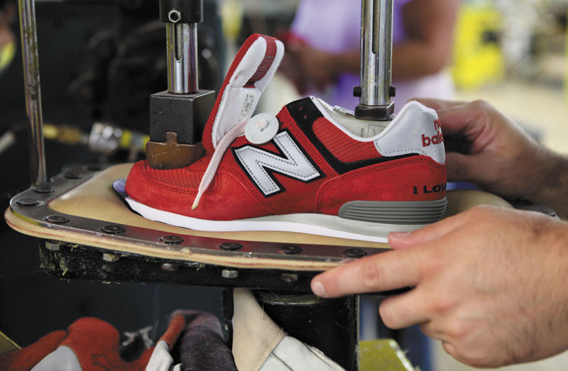 A worker uses a press to attach a shoe upper to the outsole at the New Balance factory in Norridgewock. Rep. Mike Michaud last week successfully amended an omnibus defense bill to require that the nation's military equip new recruits with sneakers manufactured in the U.S.