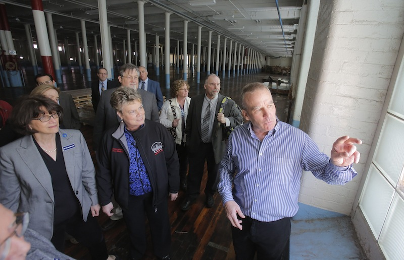 In this April 26, 2013 file photo, Doug Sanford, right, owner and developer of the North Dam Mill in Biddeford, gives a tour of the mill to state legislators of the Joint Select Committee on Maine's Workforce and Economic Future. The relatively high education level of Maine's work force is expected to spur growth in the manufacturing sector, according to a national