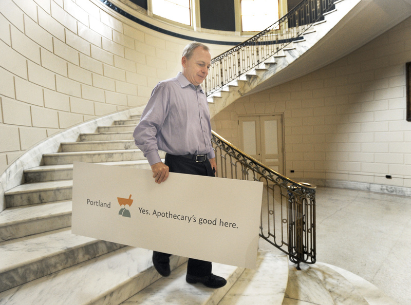Apothecary by Design managing partner Mark McAuliffe leaves Portland City Hall after the city unveiled its new brand system to promote Portland. The sign shows how the slogan can be customized. Slogan