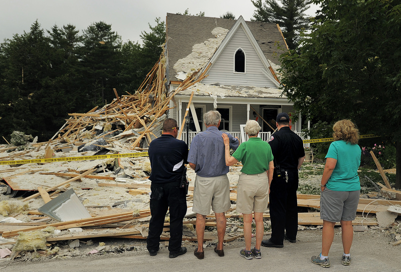 Rosemary MacKay comforts her husband, Robert, in blue, Wednesday afternoon as they survey the remains of their house at 52 Gables Drive in Yarmouth. The structure was condemned after an explosion on Tuesday killed their neighbor, Peter Corey, and severely damaged their house, along with others on the street. At left is Yarmouth fire chief Michael Robitaille, and at right is deputy chief Rich Kindelan, along with the MacKay's daughter, Alison Moore, at far right.