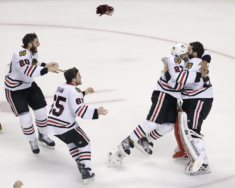 Chicago Blackhawks defenseman Johnny Oduya (27), of Sweden, hugs Chicago Blackhawks goalie Corey Crawford (50) after winning Game 6 of the NHL hockey Stanley Cup Finals 3-2 against the Boston Bruins, Monday, June 24, 2013, in Boston. (AP Photo/Charles Krupa) TD Garden