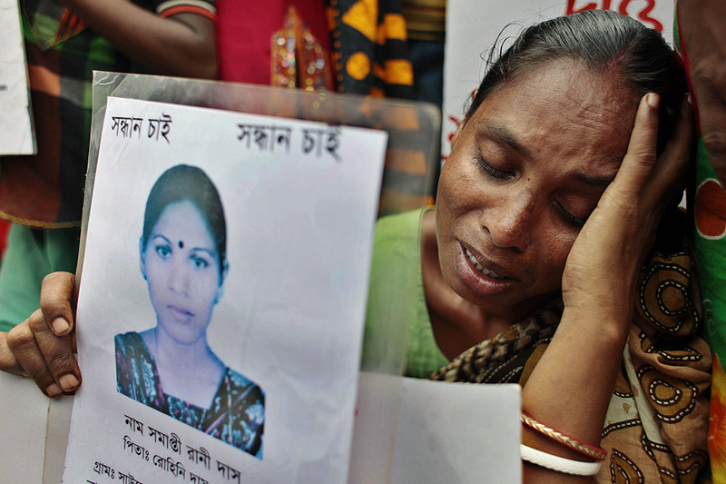 A Bangladeshi woman holds a paper with a photograph of a missing relative as she pleads for help and calls for compensation for the more than 1,100 workers who were killed in a garment-factory building collapse in April.