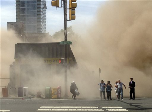 A dust cloud rises as people run from the scene of a building collapse on the edge of downtown Philadelphia on June 5, 2013, in this photo provided by Jordan McLaughlin.