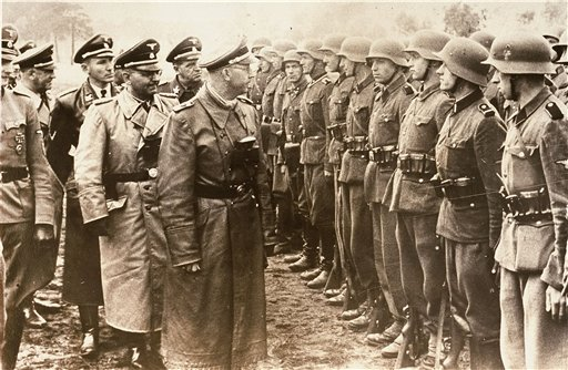 The June 3, 1944, photo provided by the U.S. Holocaust Memorial Museum shows Heinrich Himmler, center, head of the Gestapo and the Waffen-SS, and minister of the interior of Nazi Germany from 1943 to 1945, as he reviews troops of the Galician SS-Volunteer Infantry Division. Michael Karkoc a top commander whose Nazi SS-led unit is blamed for burning villages filled with women and children, lied to American immigration officials to get into the United States and has been living in Minnesota since shortly after World War II, according to evidence uncovered by The Associated Press.