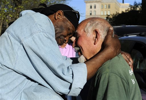 In this May 1, 2013, photo, Michael Johnson, left, hugs friend Anthony Cymerys in Bushnell Park in Hartford, Conn.