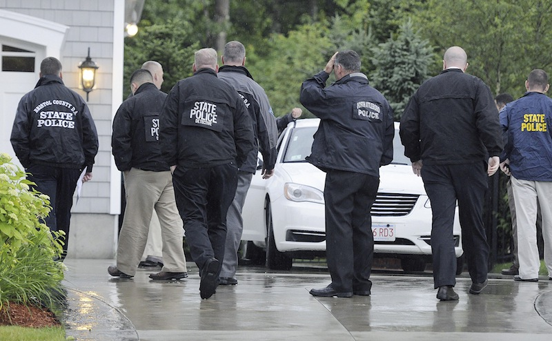 In this Tuesday, June 18, 2013 photo, state and local police gather outside the home of New England Patriot's NFL football player Aaron Hernandez in North Attleborough, Mass. Police spent hours at the home Tuesday as another group of officers searched an industrial park about a mile away where a body was discovered the day before. (AP Photo/The Sun Chronicle, Martin Gavin)