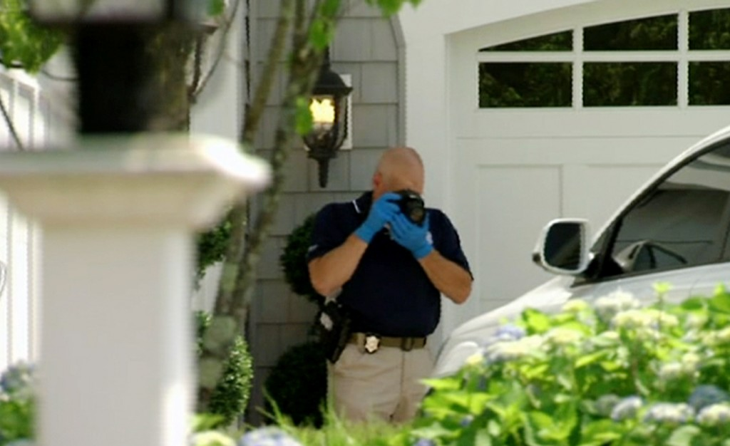 In this image taken from video, a police officer photographs a car outside the home of New England Patriots football player Aaron Hernandez, Saturday, June 22, 2013, in North Attleboro, Mass. State police officers and dogs searched Hernandez's home as they investigate the killing of Odin Lloyd, a semi-pro football player whose body was found nearby. (AP Photo/ESPN)