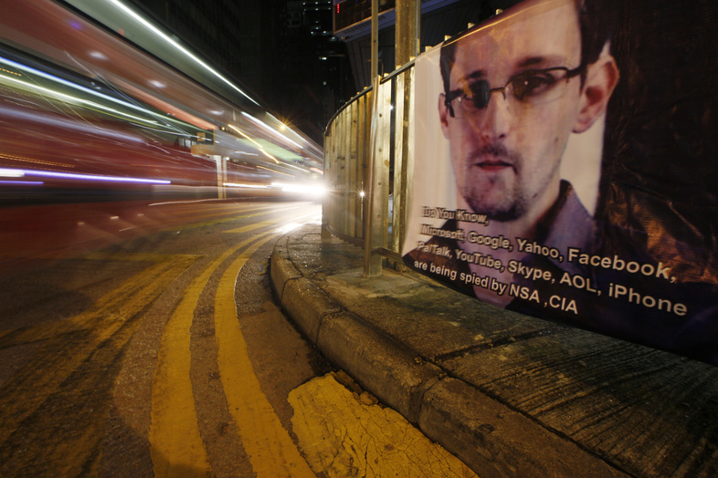 A bus drives past a banner supporting Edward Snowden, a former CIA employee who leaked top-secret documents about sweeping U.S. surveillance programs, in Hong Kong's business district this week.