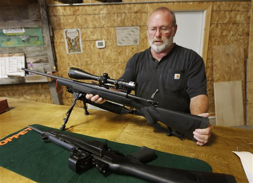 Jim Sowash handles a rifle at his gun shop near Stover, Mo., on Thursday. Sowash signed a letter to Missouri Gov. Jay Nixon urging him to sign a bill nullifying federal gun laws.