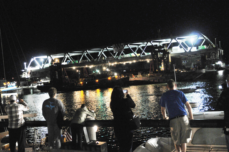 Spectators gather as the final span of the new Memorial Bridge connecting New Hampshire and Maine floats down the Piscataqua River early Monday in Portsmouth, N.H. River traffic won't be allowed for five days as the bridge is hooked up and tested.