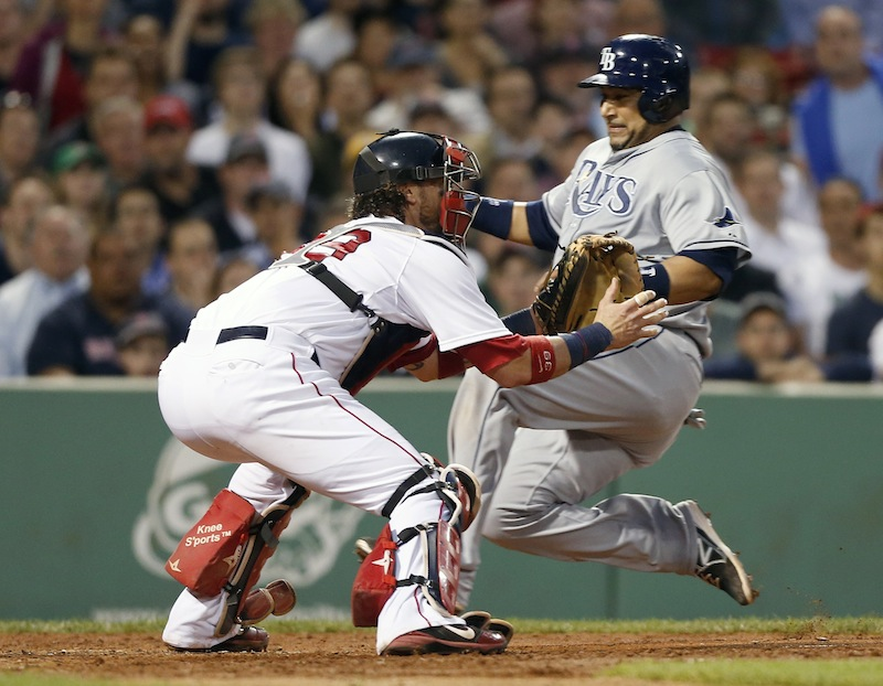 Tampa Bay Rays' Jose Molina, right, scores on an RBI single by Ben Zobrist as Boston Red Sox's Jarrod Saltalamacchia, left, waits for the throw in the fifth inning of a baseball game in Boston, Wednesday, June 19, 2013. (AP Photo/Michael Dwyer)