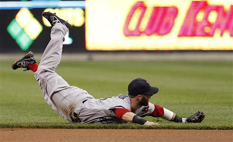 Boston second baseman Dustin Pedroia lands on the field after making a diving attempt on a single by Detroit's Andy Dirks Saturday in Detroit.