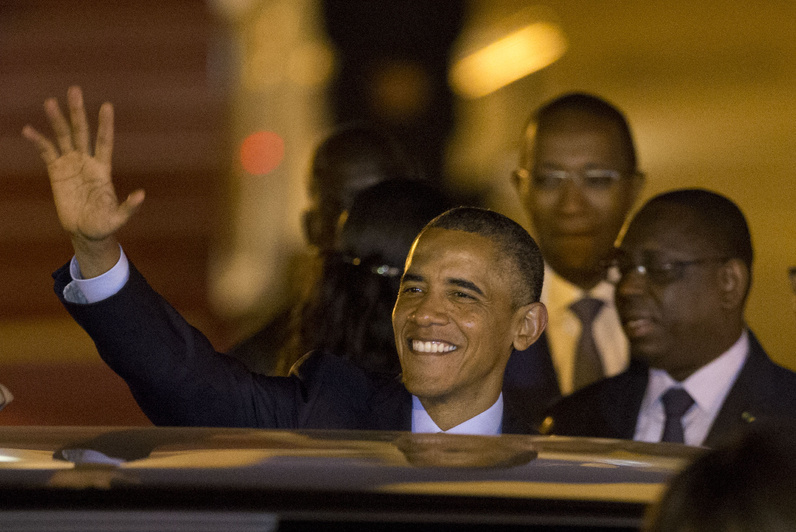 U.S. President Barack Obama waves as he gets into a car after arriving at the airport in Dakar, Senegal, on Wednesday. At right is Senegalese President Macky Sall.