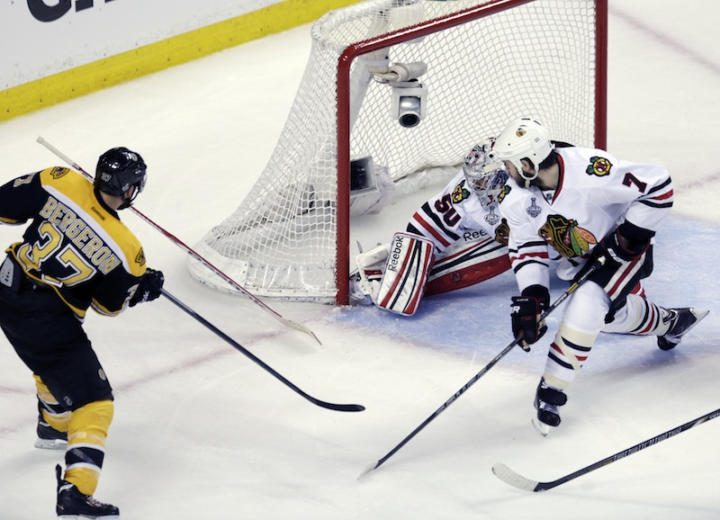 Boston Bruins center Patrice Bergeron (37) scores a goal past Chicago Blackhawks goalie Corey Crawford (50) and defenseman Brent Seabrook (7)during the second period in Game 3 of the NHL hockey Stanley Cup Finals in Boston, Monday, June 17, 2013. (AP Photo/Charles Krupa) TD Garden