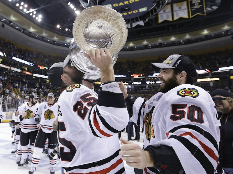 Chicago Blackhawks left wing Viktor Stalberg (25), of Sweden, hoists the Stanley Cup alongside goalie Corey Crawford (50) after the Blackhawks beat the Boston Bruins [score] in Game 6 of the NHL hockey Stanley Cup Finals Monday, June 24, 2013, in Boston. (AP Photo/Elise Amendola) TD Garden