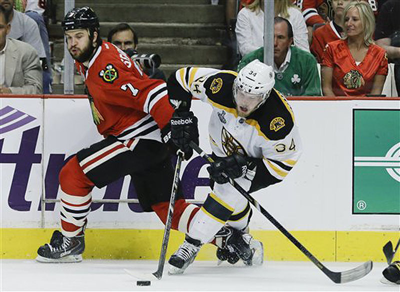 Chicago Blackhawks defenseman Brent Seabrook gets tangled up with Boston Bruins center Carl Soderberg during Game 5 of the NHL hockey Stanley Cup Finals on Saturday in Chicago.