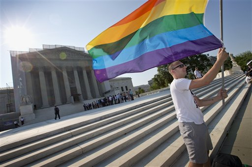 Vin Testa of Washington waves a rainbow flag in support of gay rights outside the Supreme Court in Washington on Tuesday. The broadest possible ruling by the court would give gay Americans the same constitutional right to marry as heterosexuals.